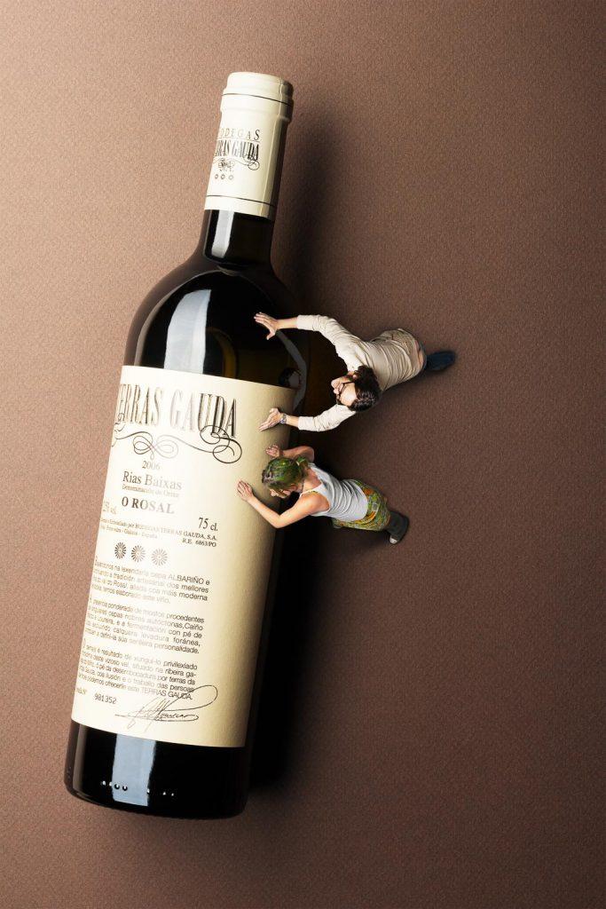Weinflasche wird von zwei Menschen geschoben