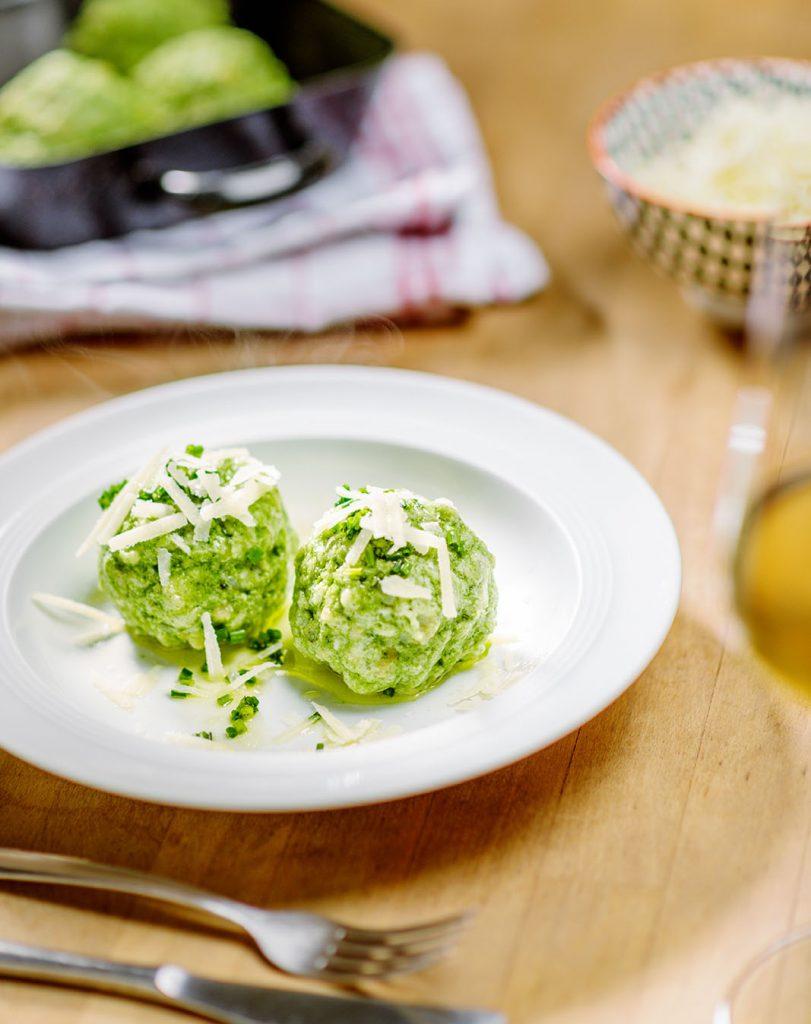 Spinatknödel im Teller mit Parmesan
